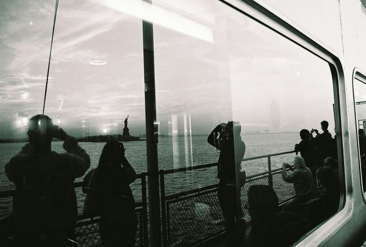 Reflection Of People Photographing Statue Of Liberty While Traveling In Boat