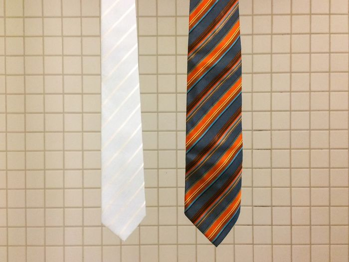 Close-Up Of Neckties Hanging Against Tiled Wall