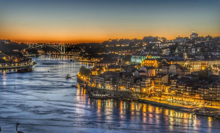 Illuminated buildings in porto at sunset