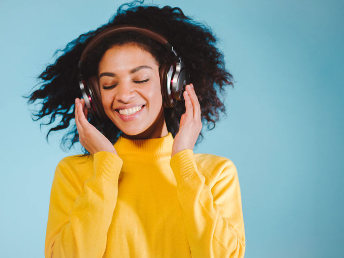 Close-Up Of Woman Enjoying Music On Headphones Against Blue Background