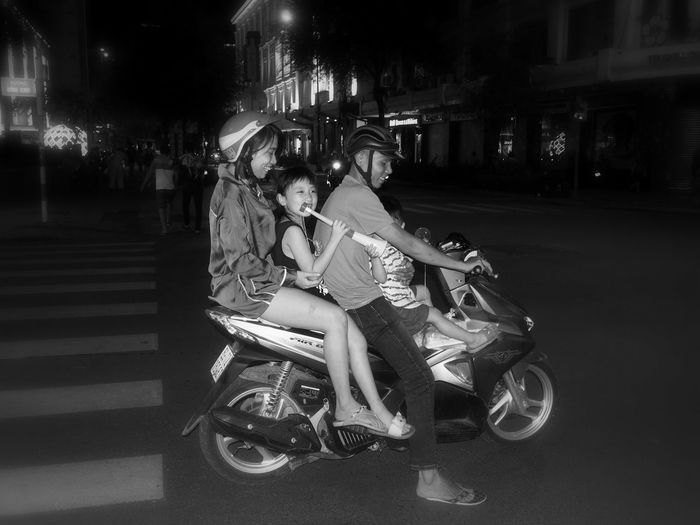 Family of 4 on a scooter, celebrating the victory of the Vietnam football team. In Ho-Chi-Minh City City Night Transportation Child Helmet Riding Street Mode Of Transportation Four People On Motorbike Scooter Trumpet Full Length Illuminated Bnw_friday_eyeemchallenge Bnw_motorcycles