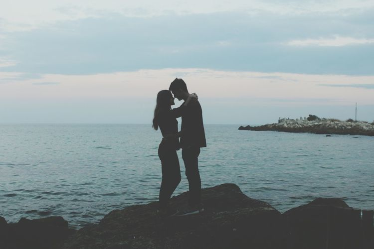 Couple kissing on sea against sky