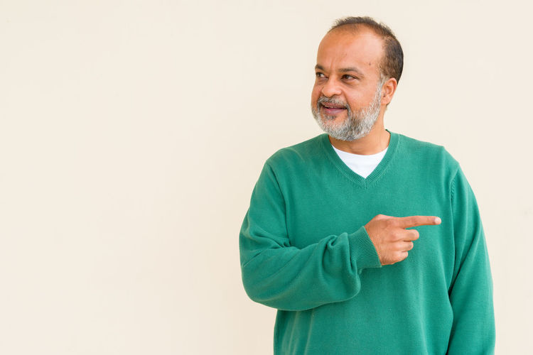 Happy man standing against white background