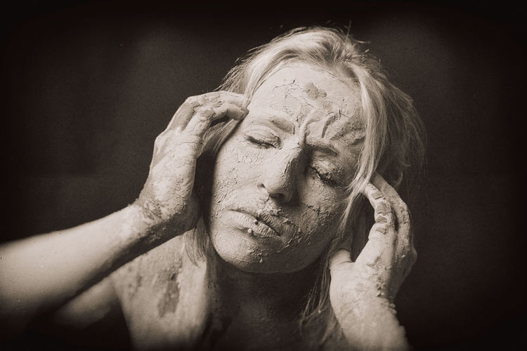 High angle view of young woman covered with mud
