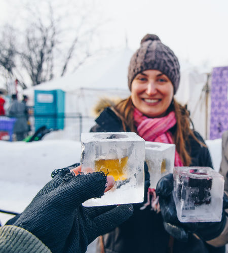 Friends toasting drinks while standing outdoors during winter