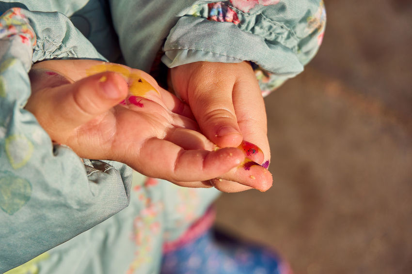 A child with paint on her hands rubbing them Human Hand Hand Human Body Part Holding People Body Part Child Women Close-up Focus On Foreground Togetherness Real People Females Midsection Family High Angle View Care Finger Nail Receiving Paint Hands Rubbing Painted Hands