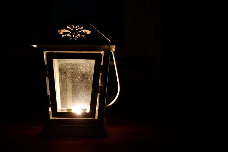 Close-up of illuminated lamp on table against black background