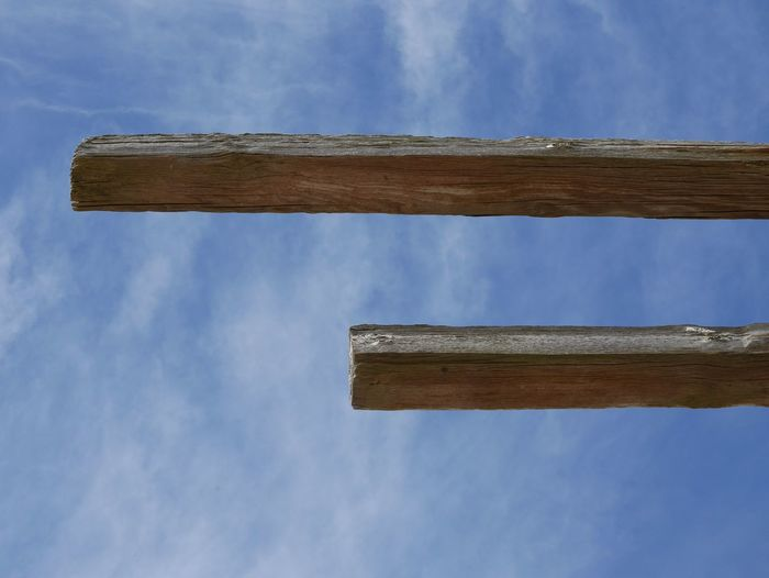 Low angle view of wooden planks against cloudy blue sky