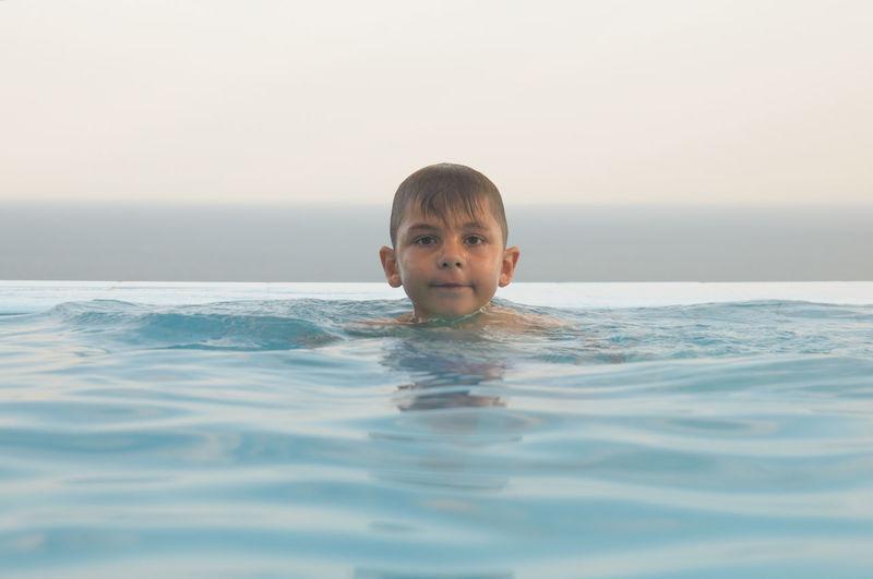 Portrait of boy swimming in infinity pool