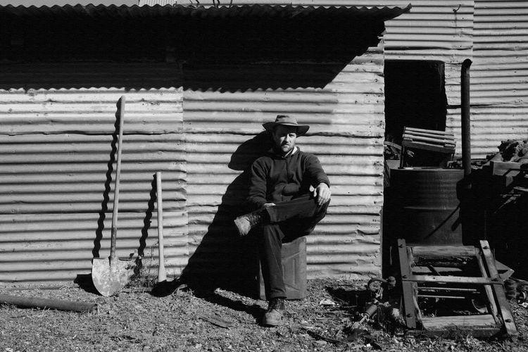 Full length of man sitting against abandoned house