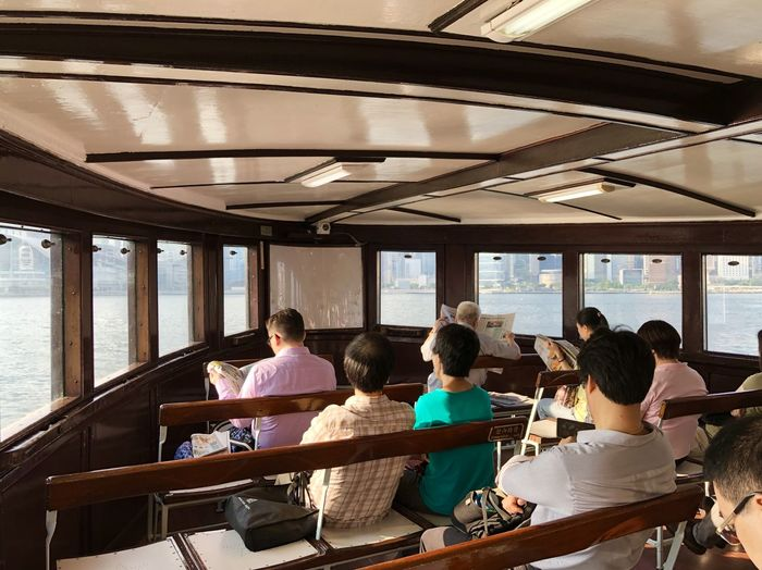 Rear view of people sitting in ferry on lake