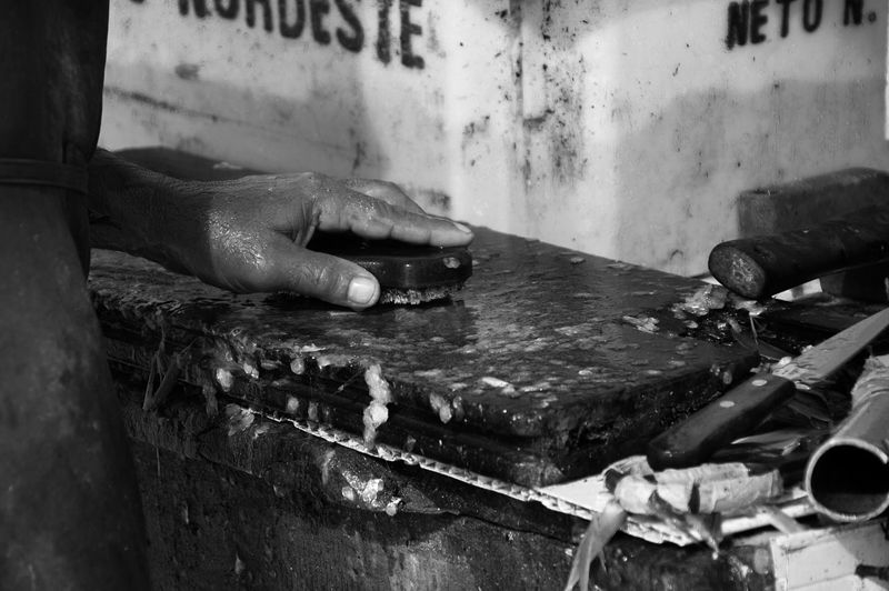Cropped image of hand cleaning cutting board at fish market