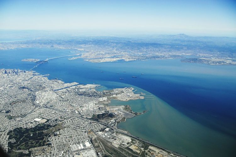 Aerial view of cityscape and bay against sky