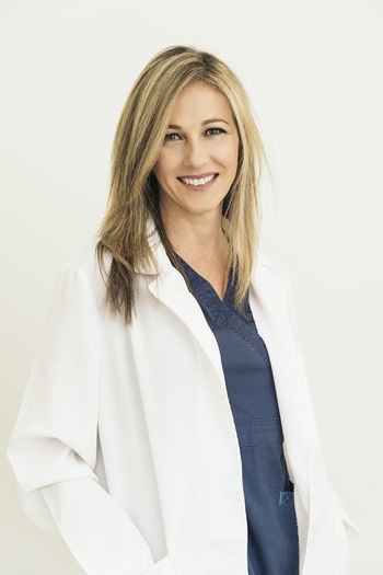 Portrait of female doctor smiling while standing against white background