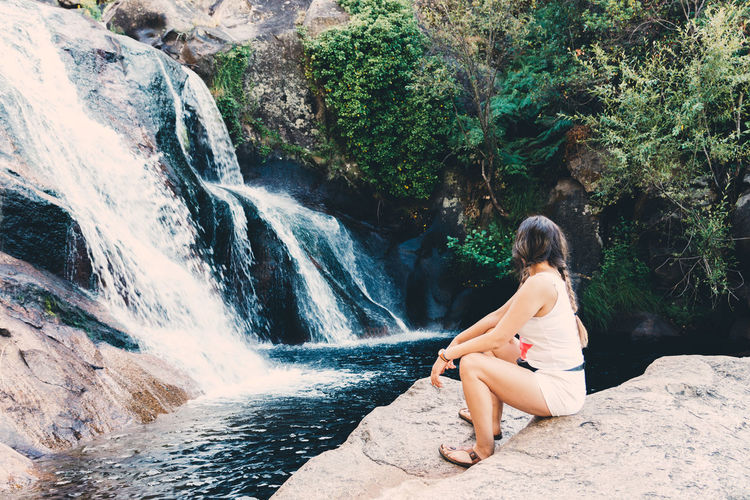 Rear view of woman sitting on rock against waterfall