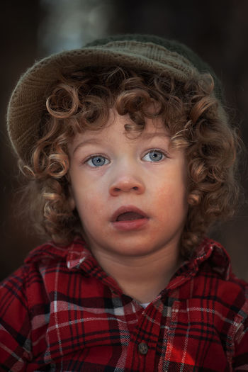 Child Childhood Portrait Headshot Front View One Person Curly Hair Innocence Boys Cute Real People Close-up Males  Looking At Camera Lifestyles Hair Hairstyle Making A Face Contemplation 2 Years Old 2 Years Old Kid Warm Colors Warm Lighting Colors Hat Forest