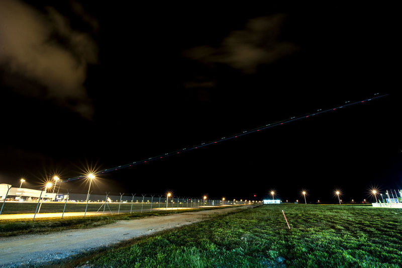 Light trails on street against sky at night