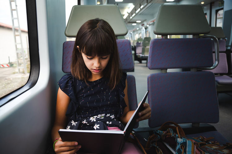 Girl reading book while sitting in train