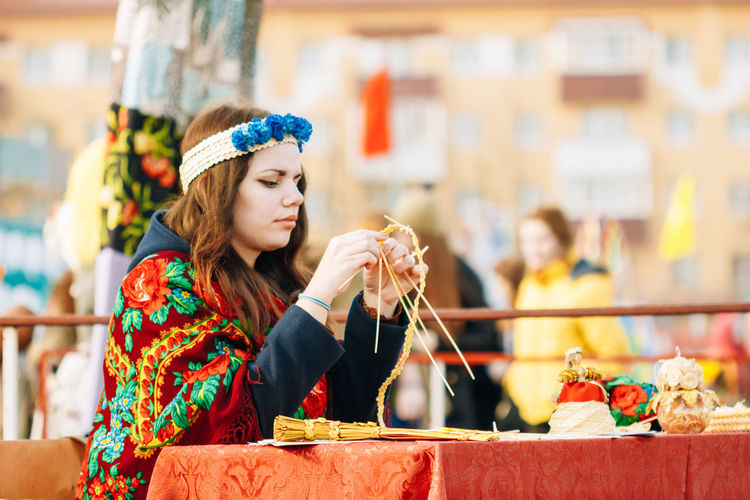 Gomel, Belarus - March 12, 2016: Beautiful young girl in a national Belarusian dress is engaged in manual work. Shrovetide Maslenitsa Belarus Celebration Gomel National Needlework Woman Young Beautiful Woman Culture Day Editorial  Ethnic Famele Folk Girl Maslenitsa One Person Outdoor People Portrait Shrovetide Sitting Traditional Turism Young Women