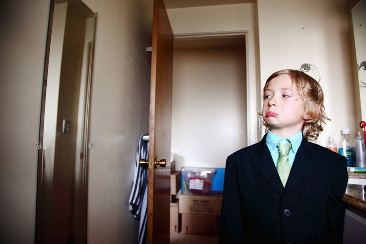 Boy in suit making face while standing in bathroom
