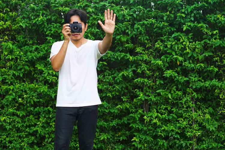 Full length of man photographing against plants
