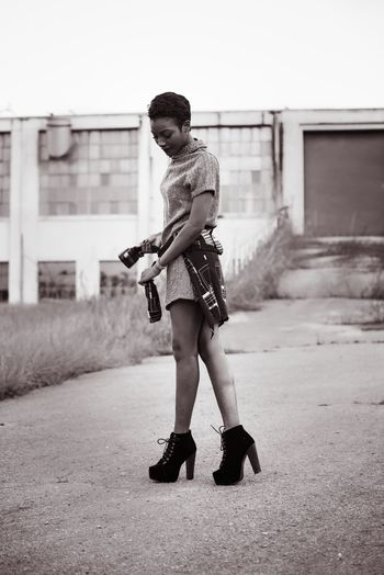 Fashionable Woman Tying Shirt On Road
