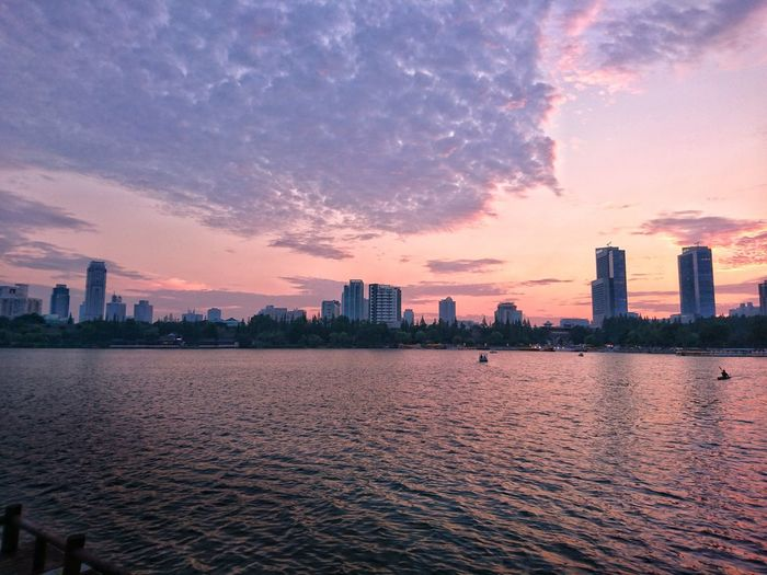 River by cityscape against sky during sunset