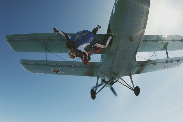 Low angle view of people jumping from biplane against clear sky