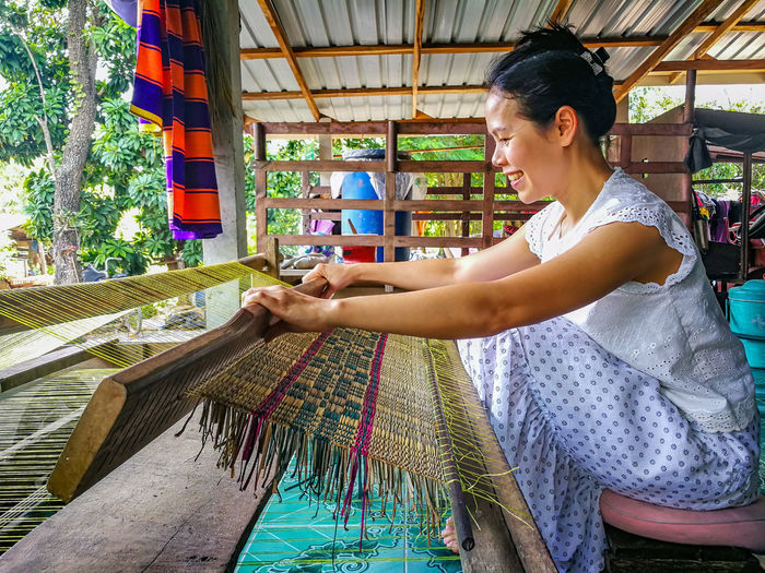 Side view of smiling woman weaving carpet at workshop