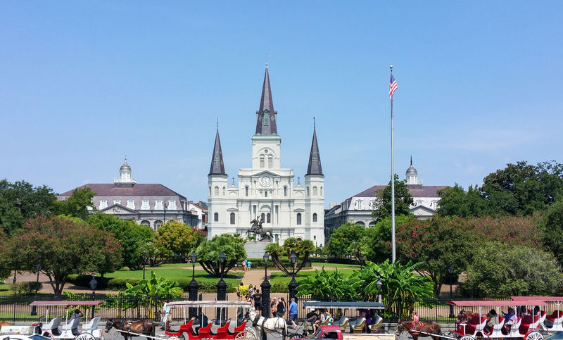 Jackson Square, with Jackson's statue at center, and Saint Louis Cathedral Church Jackson New Orleans New Orleans, LA Slavery Statue Andrew Jackson Architecture Building Exterior Built Structure Clear Sky Crowd Day Large Group Of People Nature Outdoors People Place Of Worship Real People Religion Saint Louis Cathedral, Sky Spirituality Travel Destinations Tree