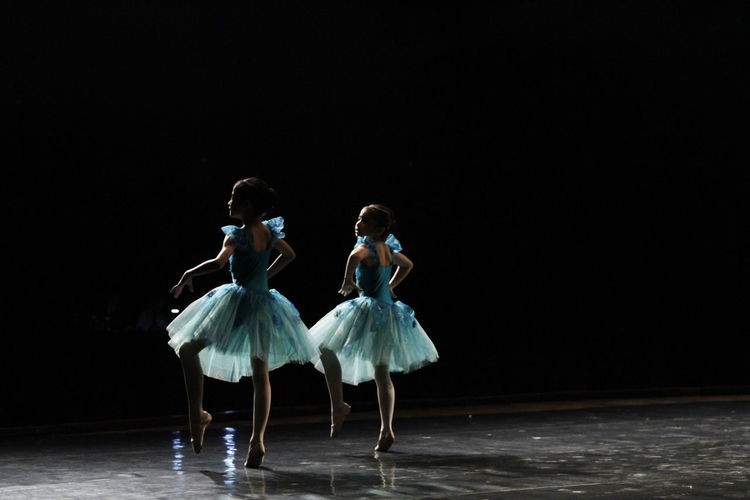 Group of people dancing against black background