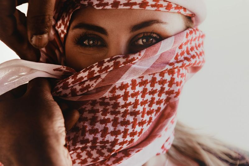 Close-up portrait of young woman covering face with headscarf