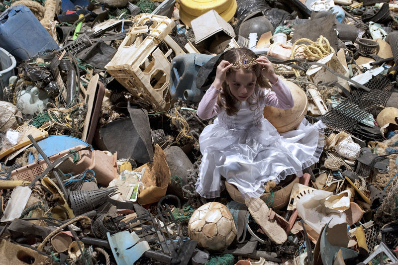 High angle view of girl sitting in garbage