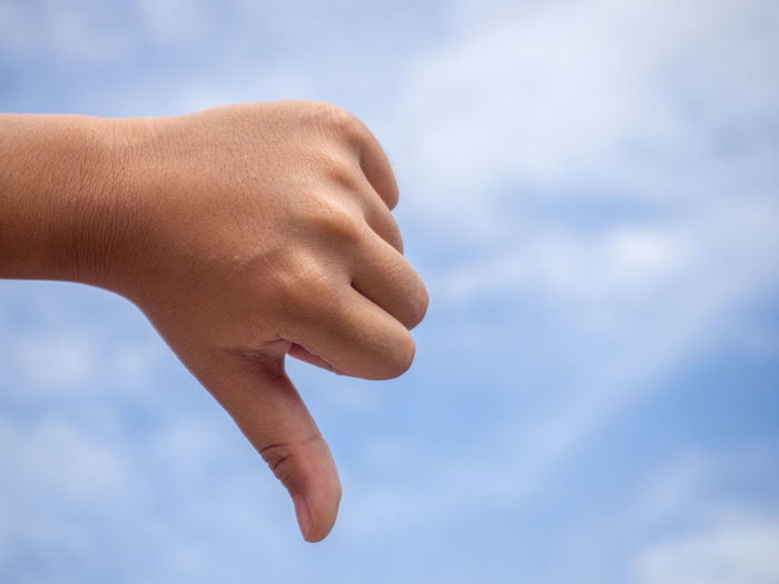 Cropped hand of person gesturing thumbs down against cloudy sky
