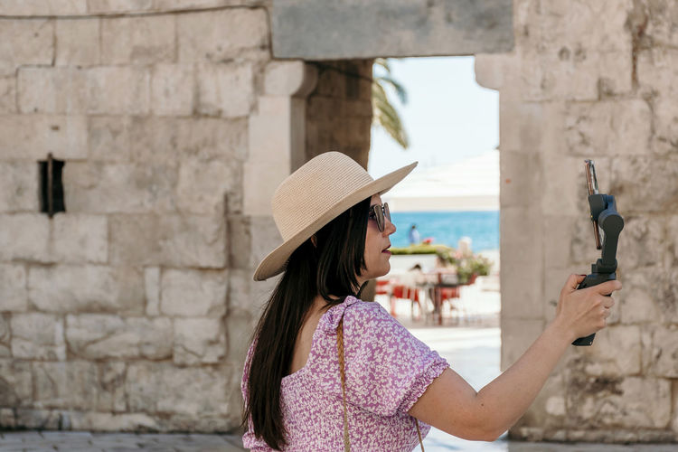 Side view of woman holding mobile phone against wall