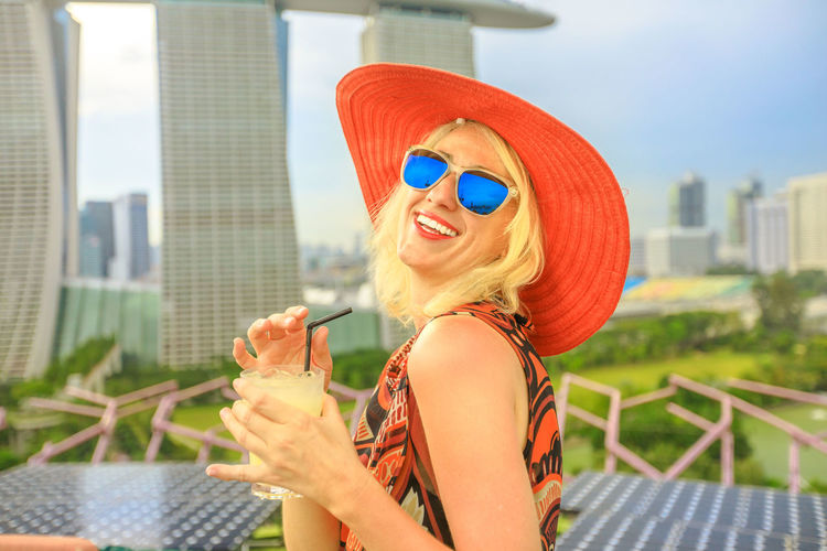 Lifestyle caucasian woman in wide hat drinking orange juice at rooftop cityscape skyline. Tourist enjoying above aerial view of Singapore marina. Travel holiday vacation in Singapore, Southeast Asia. Singapore Singapore City Woman Tourist Tourist Attraction  Tourist Destination People Girl Females Aerial View Skyline Cityscape Panorama Happy Travel Hat Lifestyle Enjoy Nature Tourism Smiling Aperitif Drink Orange Juice  Analcolic Glass Fashion Lifestyles Architecture One Person Glasses Happiness Sunglasses Leisure Activity Women Young Women Real People Built Structure City Young Adult Portrait Beautiful Woman Casual Clothing Hair Hairstyle Outdoors
