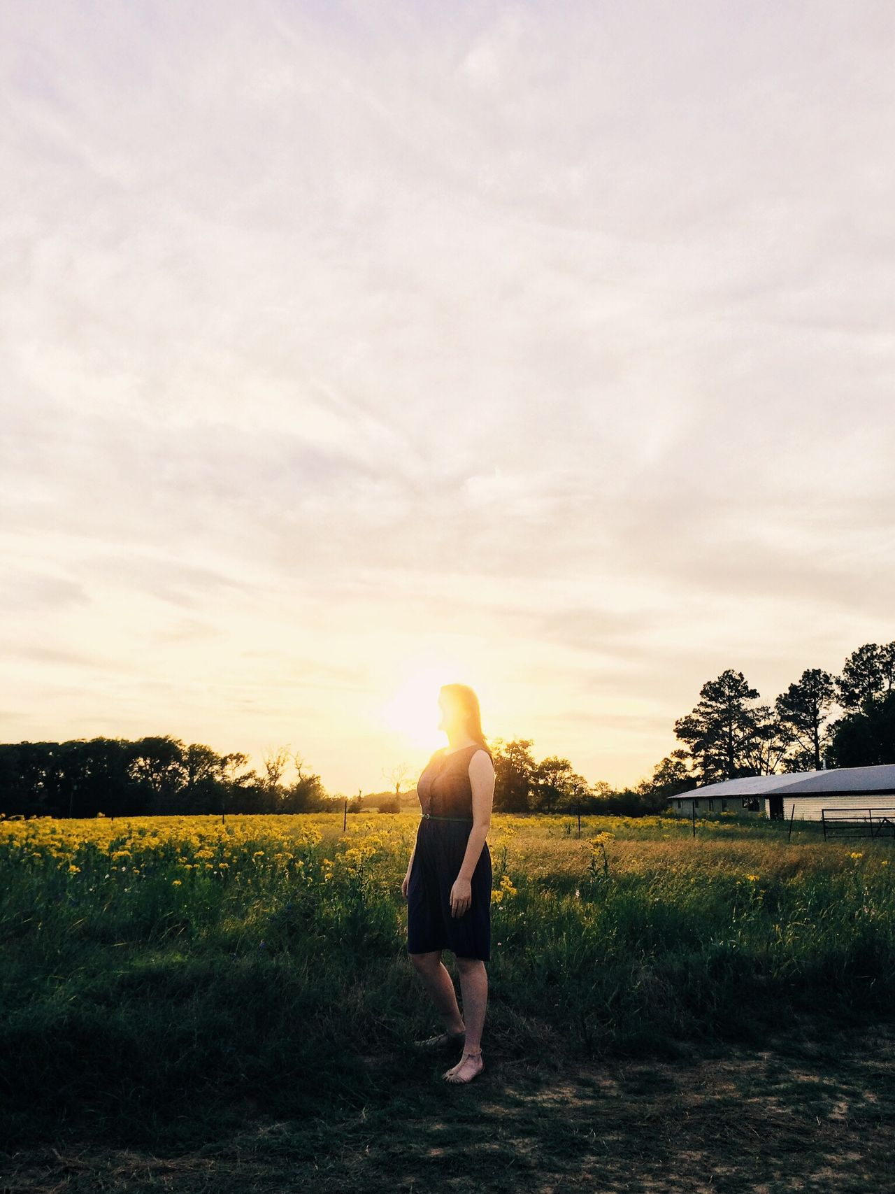 Woman standing on grassy field against cloudy sky during sunset