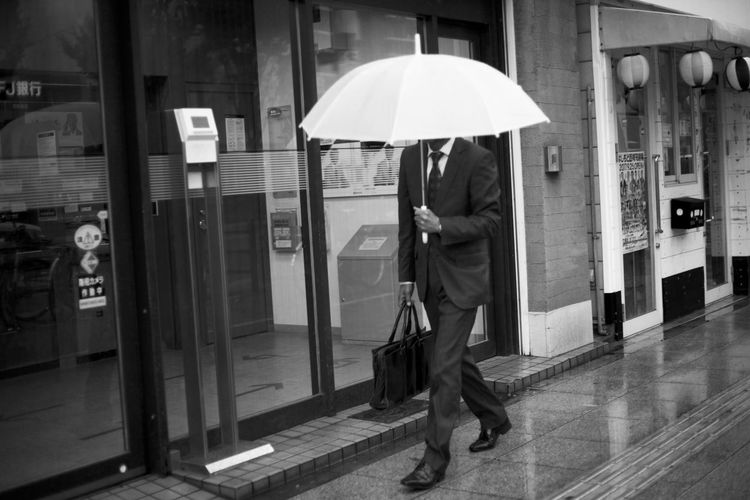 Full length of man with umbrella walking in city during rainy season