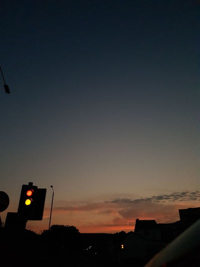 Silhouette of traffic signal against sky during sunset