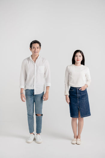 Portrait of couple of young happy married hipsters Portrait Full Length Front View Studio Shot Looking At Camera Two People Indoors  Standing Casual Clothing Young Adult Smiling Emotion Togetherness Women Men People Females Young Men Gray Adult Couple - Relationship Jeans Hairstyle Hipster