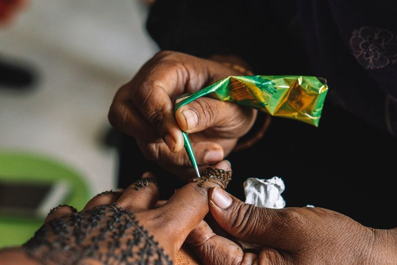 Midsection of person making henna tattoo on woman hand