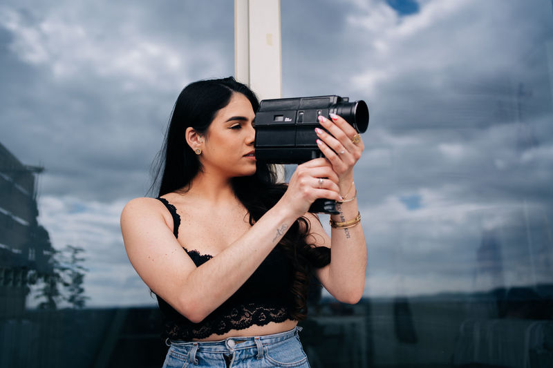 Young woman holding camera while standing against sky