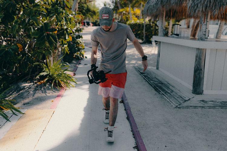 Portrait of man walking on footpath