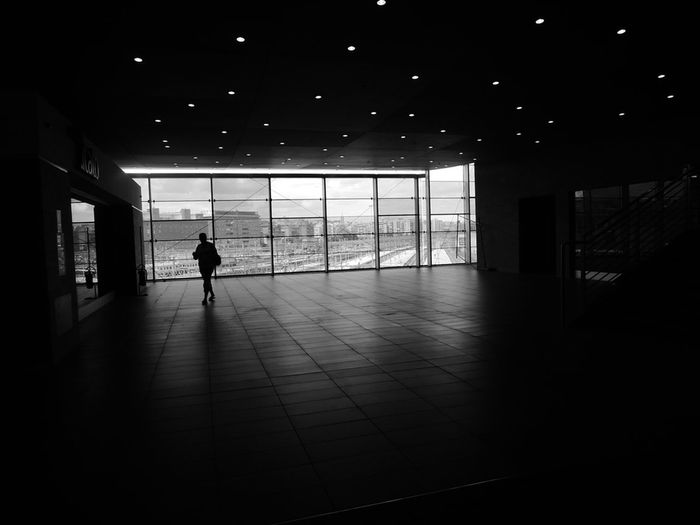 Full length of woman walking through dark corridor
