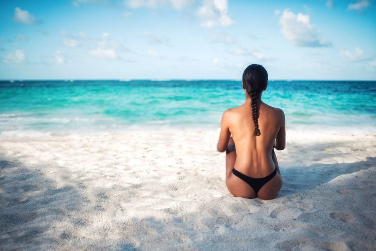 Rear View Of Shirtless Woman Sitting On Sand Beach Against Sky