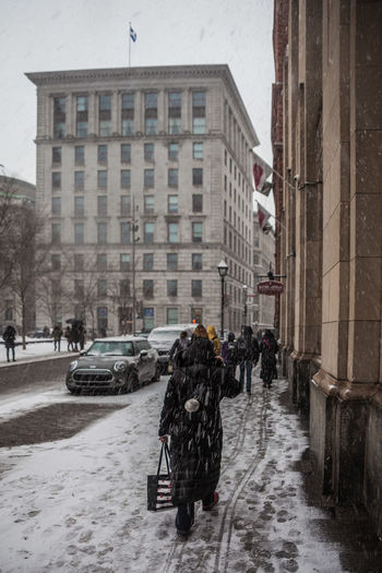 Architecture Building Exterior Built Structure City Cold Temperature Day Outdoors People Real People Rear View Snow Snowing Street Winter