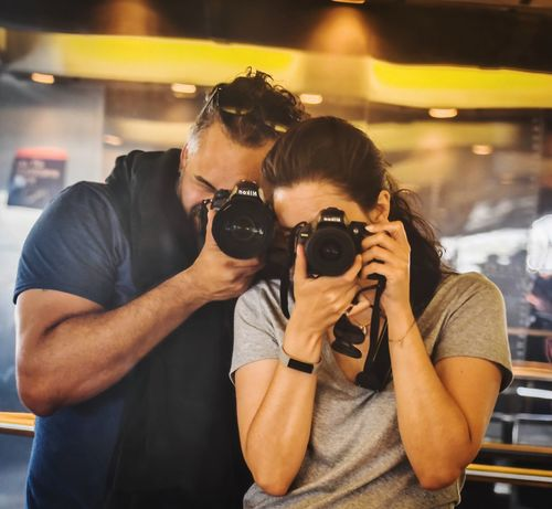 Photography Themes Camera - Photographic Equipment Photographing Technology Holding Lifestyles Front View Casual Clothing Portrait Focus On Foreground Activity Occupation Real People Indoors  Two People Young Men People Photographer Leisure Activity Adult