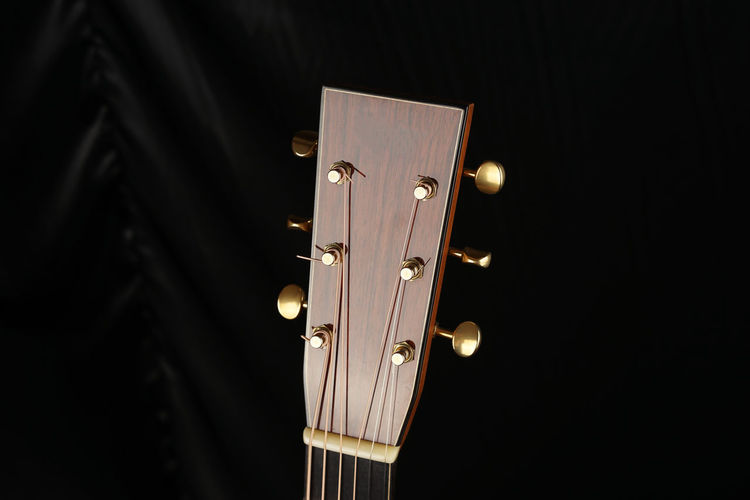 Cropped Image Of Acoustic Guitar On Bed
