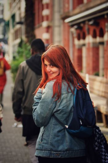 Redhead woman smiling while standing on sidewalk in city