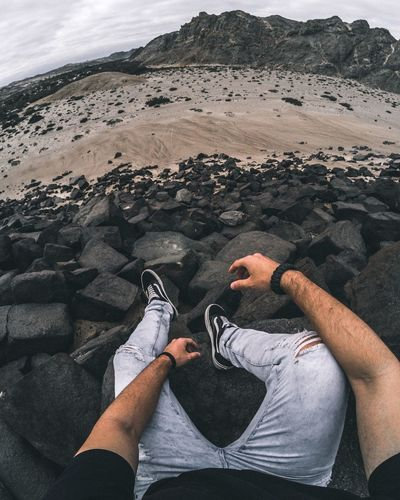 High angle view of man sitting on rock